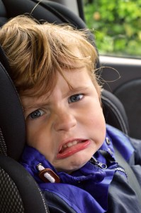 Grandchild with angry face sitting in carseat - traveling with grandchildren - Adventures in NanaLand