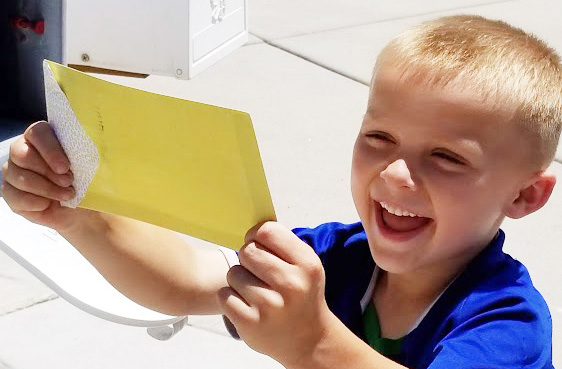 Happy child getting a letter from a mailbox - Ways to Be an Awesome Long Distance Grandparent - Adventures in NanaLand