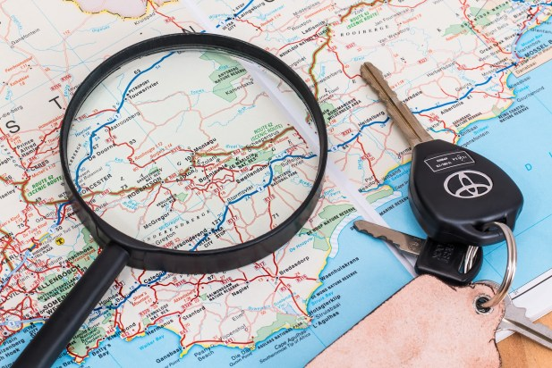 Map with a magnifying glass and keys sitting on top - traveling with grandchildren - Adventures in NanaLand