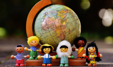 Dolls from around the world standing next to a globe, subscription boxes for kids, Adventures in NanaLand