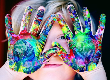 boy with colorful paint all over hands in front of his face - Adventures in NanaLand - Things to do with grandkids