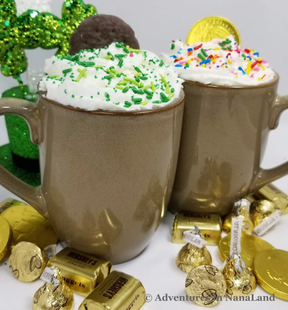 2 mugs of hot chocolate with whipped cream - one with green sprinkles and one with rainbow sprinkles, gold foil-wrapped chocolates St. Patrick's Day Activities- Adventures in NanaLand
