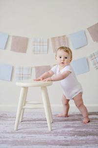 Baby standing at small wooden stool - Adventures in NanaLand