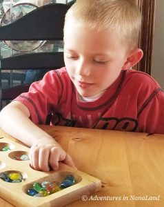 Boy playing Mancala - Best Games for Families to Play Together - Adventures in NanaLand