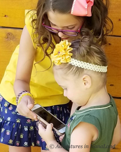 Girls looking at cell phone together - Living far away from grandchildren - Adventures in NanaLand