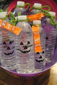 Water bottles with pumpkin faces drawn on the front with a packet of orange-flavored drink attached- Non-candy Halloween treats - Adventures in NanaLand