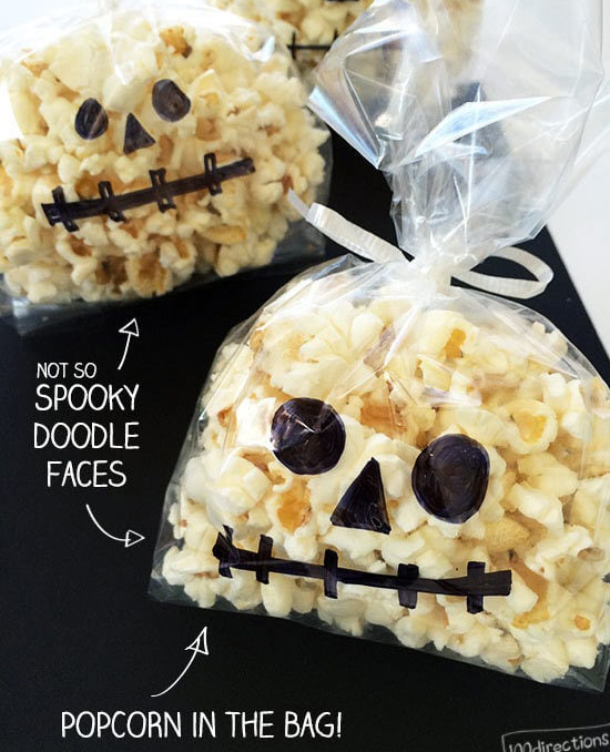 Plastic bags of popcorn with spooky faces drawn on bag - 100 Directions.com