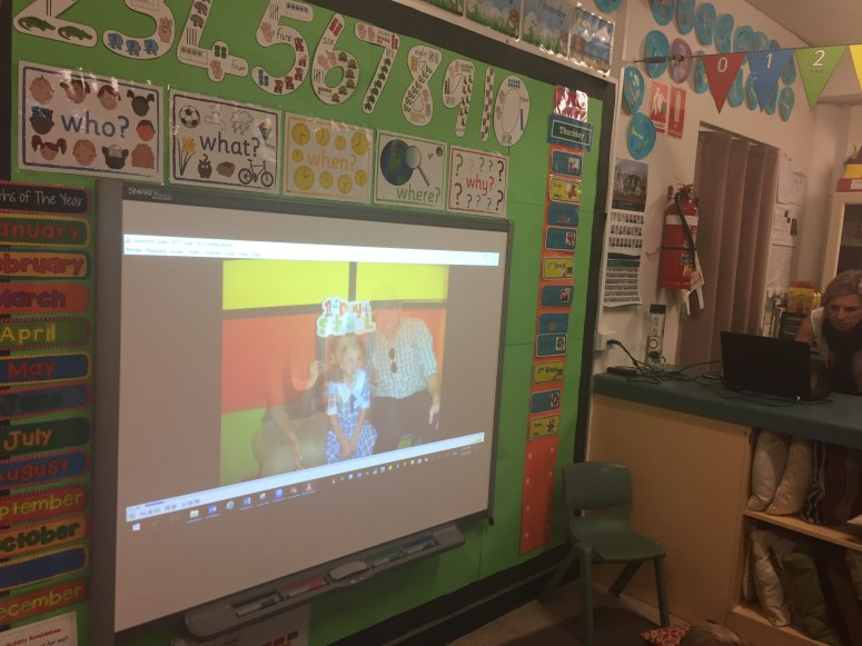 An image of a child's classroom showing a large screen with images and bright coloured pages all around the screen.