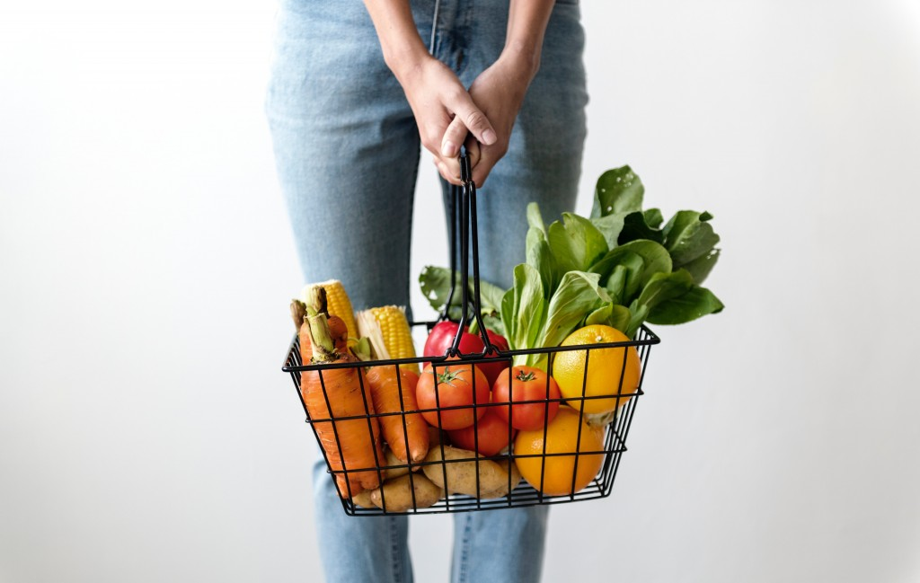 person holding a basket of fresh vegetables