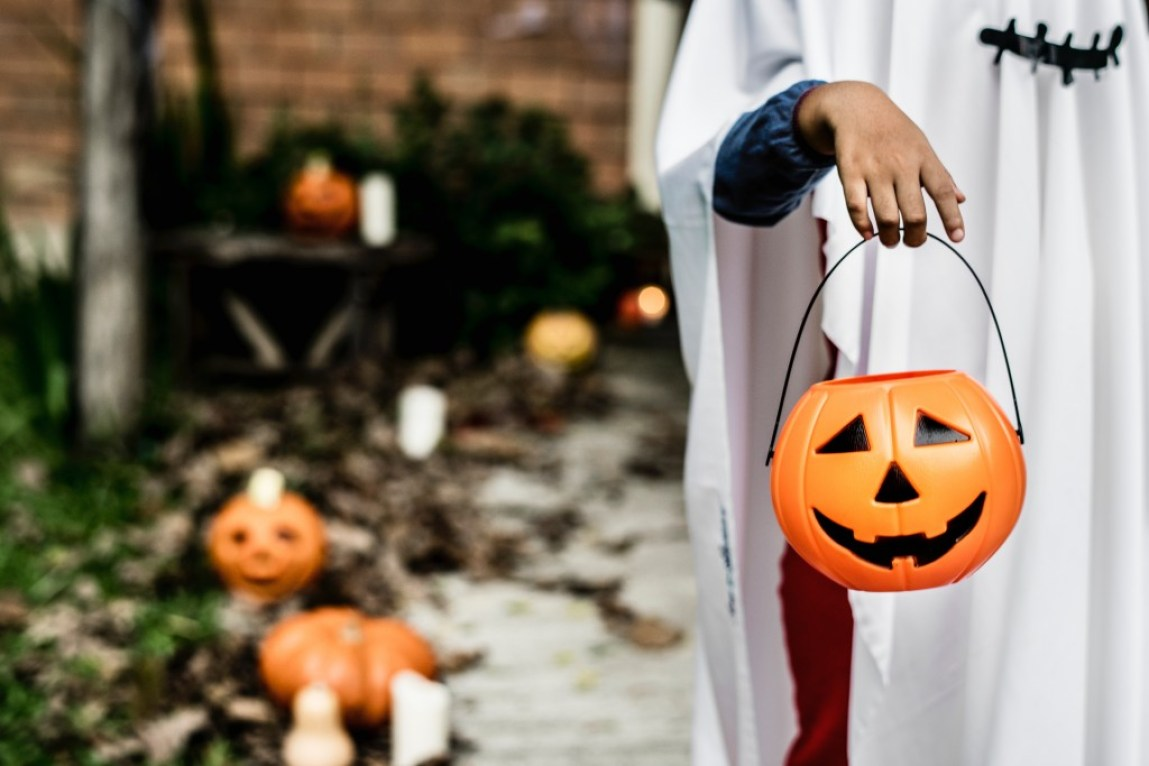 child dressed as ghost holding pumpkin candy pail