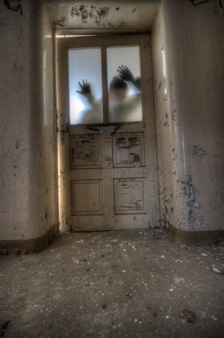 silhouette behind door of dilapidated house