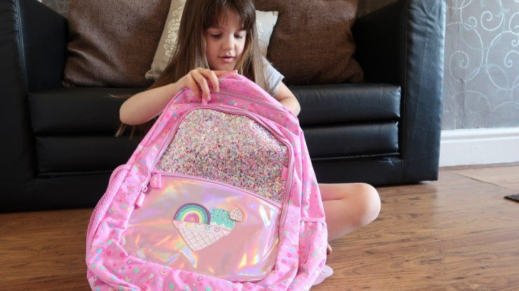 girl looking inside ther sparkly pink smiggle backpack
