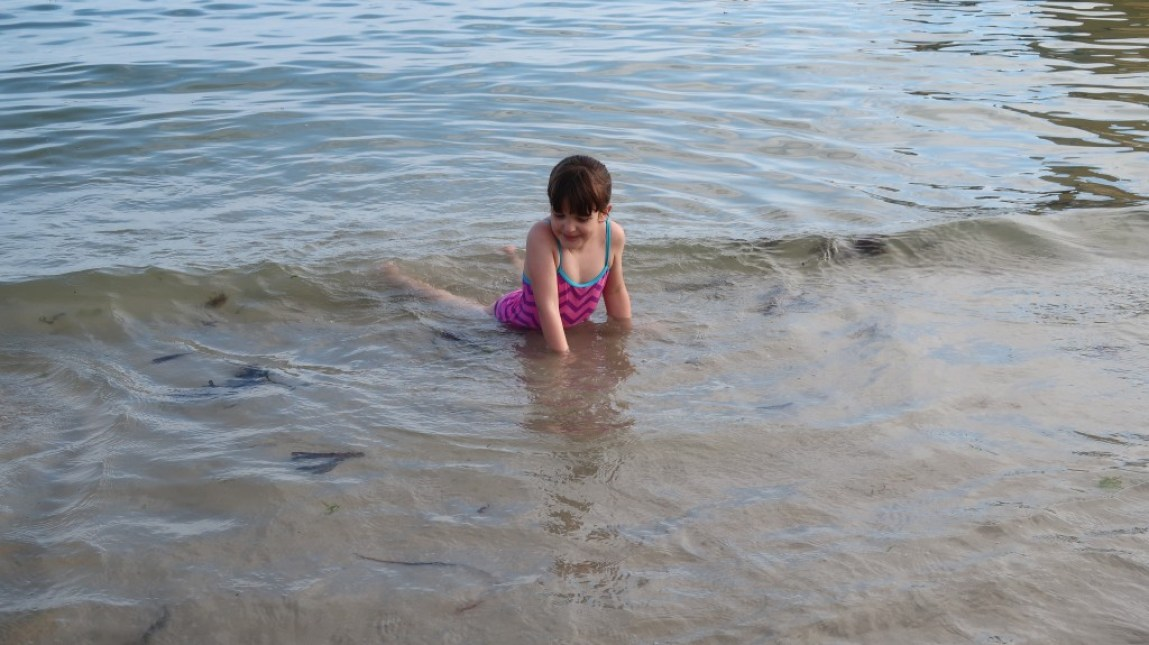 girl swimming in sea opposite Ommaroo Hotel In Jersey