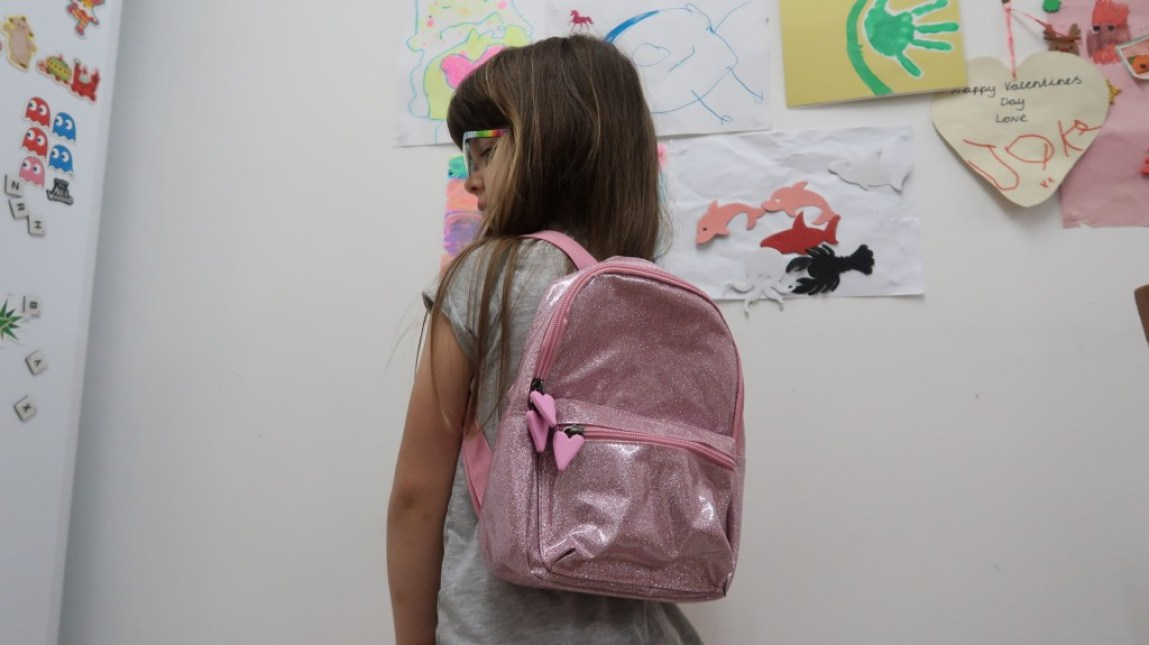 girl wearing sparkly pink backpack