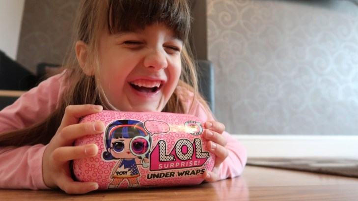 child laughing with L.O.L Surprise! Eye Spy Under Wraps