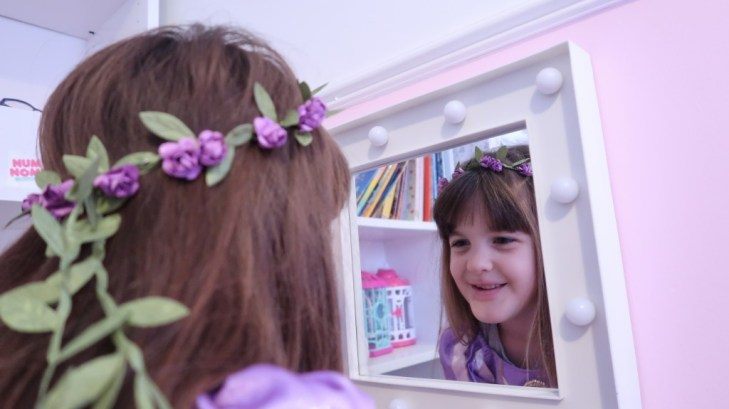 pretty girl with flowers in her hair looking into mirror