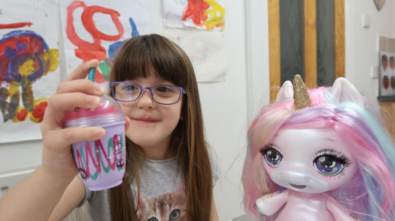 girl feeding poopsie unicorn with feeding bottle