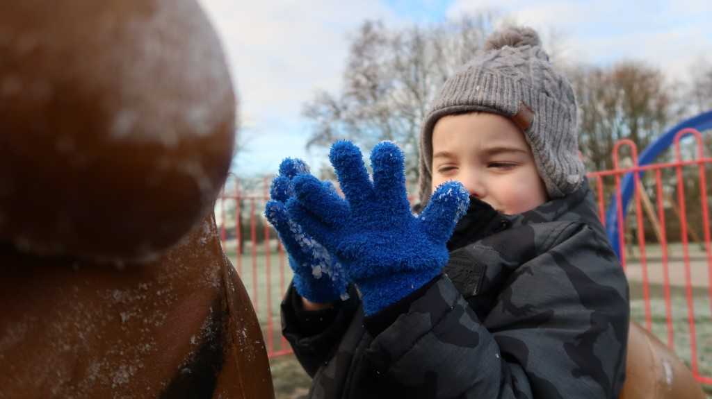 little boy with blue gloves on