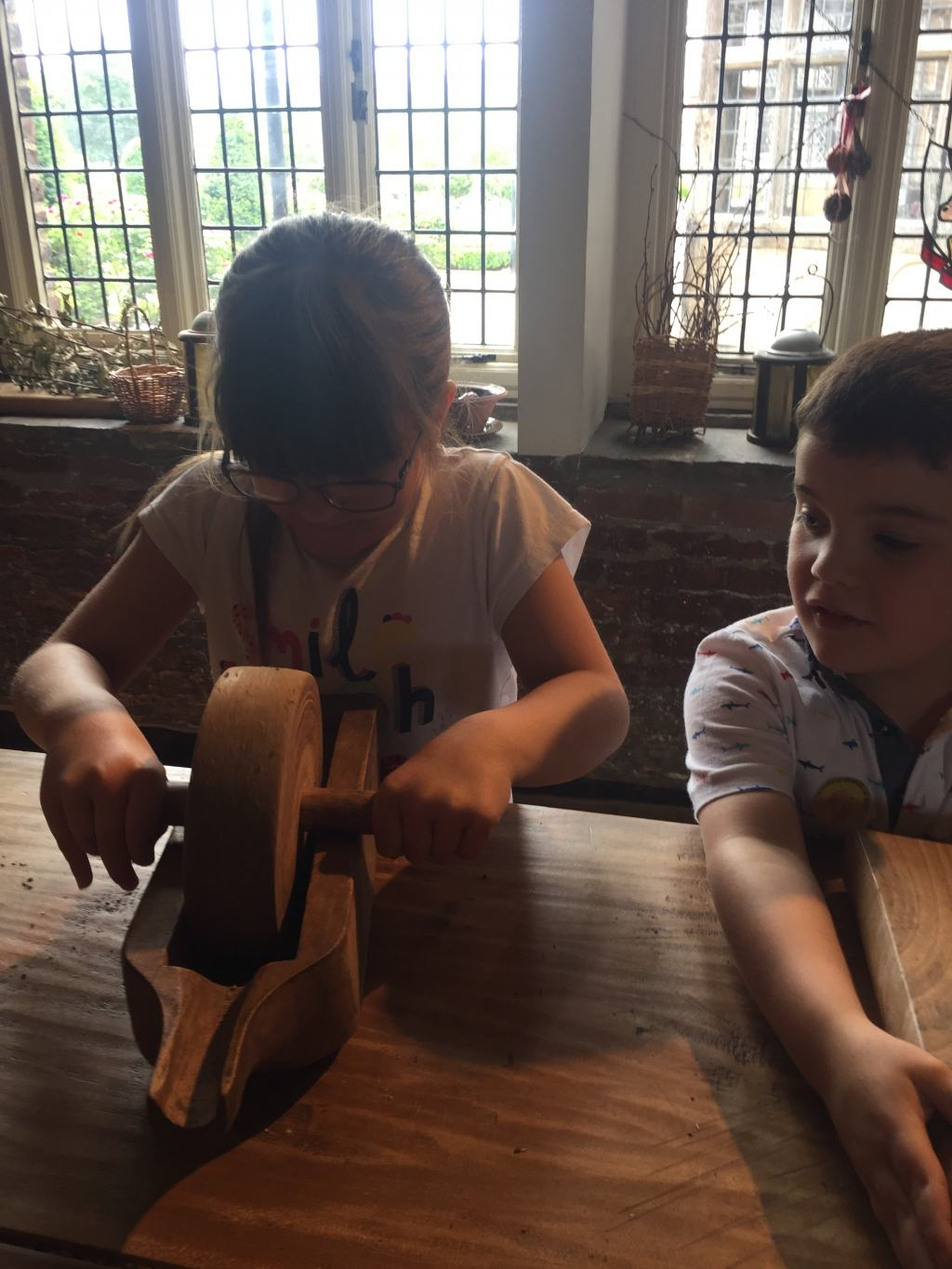 children learning how to grind herbs in a tudor kitchen