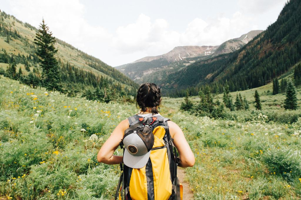 woman with backpack looking at mountains