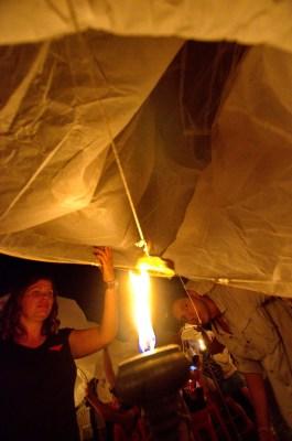 Daniel and Caz start lighting the lantern on fire