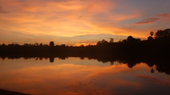 Sun rising over the moat of Angkor Wat