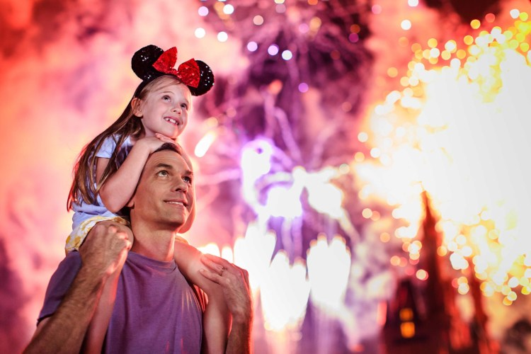 Family creating memories at evening fireworks at the Walt Disney World Magic Kingdom park
