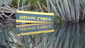 Inverted sign displaying reflected Mirror Lakes image, near New Zealand's Earl Mountains
