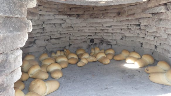 Sourdough bread baking in a traditional clay oven