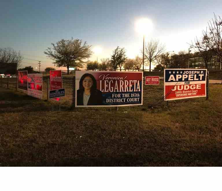 More political signs wrapping a fence