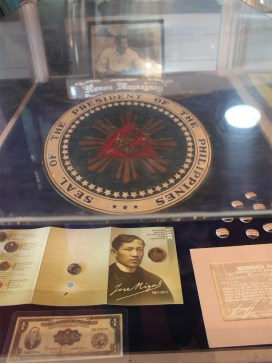 Seal of the Philippine President; Photo of Jose Rizal in the foreground