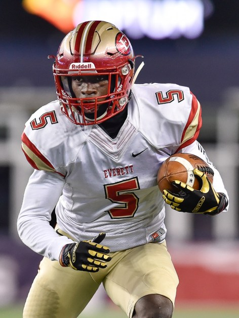 Mike Sainristil of Everett carries the ball as he is trailed by Justin Wenstrom of Xaverian during their 35-10 MIAA Div. 1 Super Bowl win at Gillette Stadium, Saturday, Dec. 2, 2017.