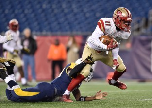 Anthony Norcia of Everett carries the ball as he is wrapped up by an Xaverian player during their 35-10 MIAA Div. 1 Super Bowl win at Gillette Stadium, Saturday, Dec. 2, 2017.