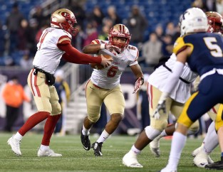 Everett quarterback Jake Willcox hands the ball off to Kevin Brown during their 35-10 MIAA Div. 1 Super Bowl win over Xaverian at Gillette Stadium, Saturday, Dec. 2, 2017.