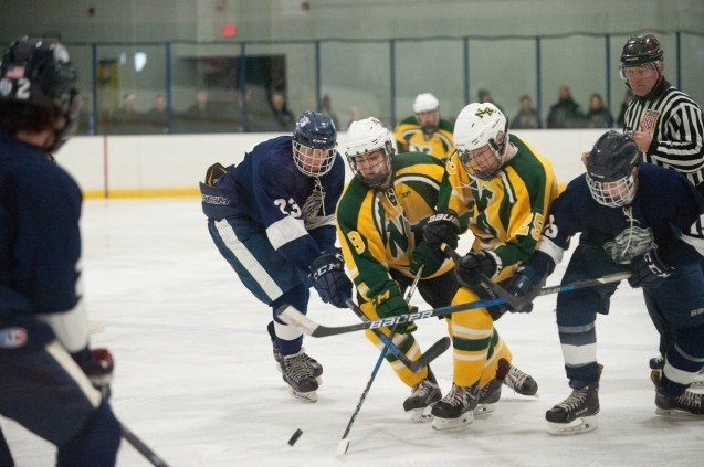 John Simonetti (left) and Jack Hammersley battle North Reading forwards for the puck.