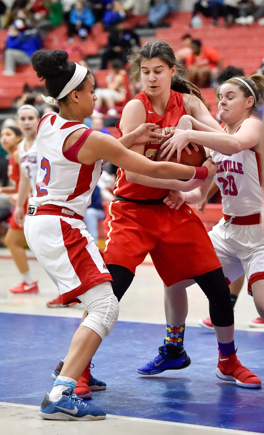 Carolann Cardinale of Everett holds onto the ball as two Somerville players challenge her during their game at Somerville High School on Tuesday, Feb. 13, 2018.