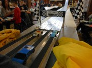 SPEEDING TO THE END: Cars cruising down the track at an estimated 200 miles per hour zoomed past the finish line at last Saturday's Pinewood Derby.