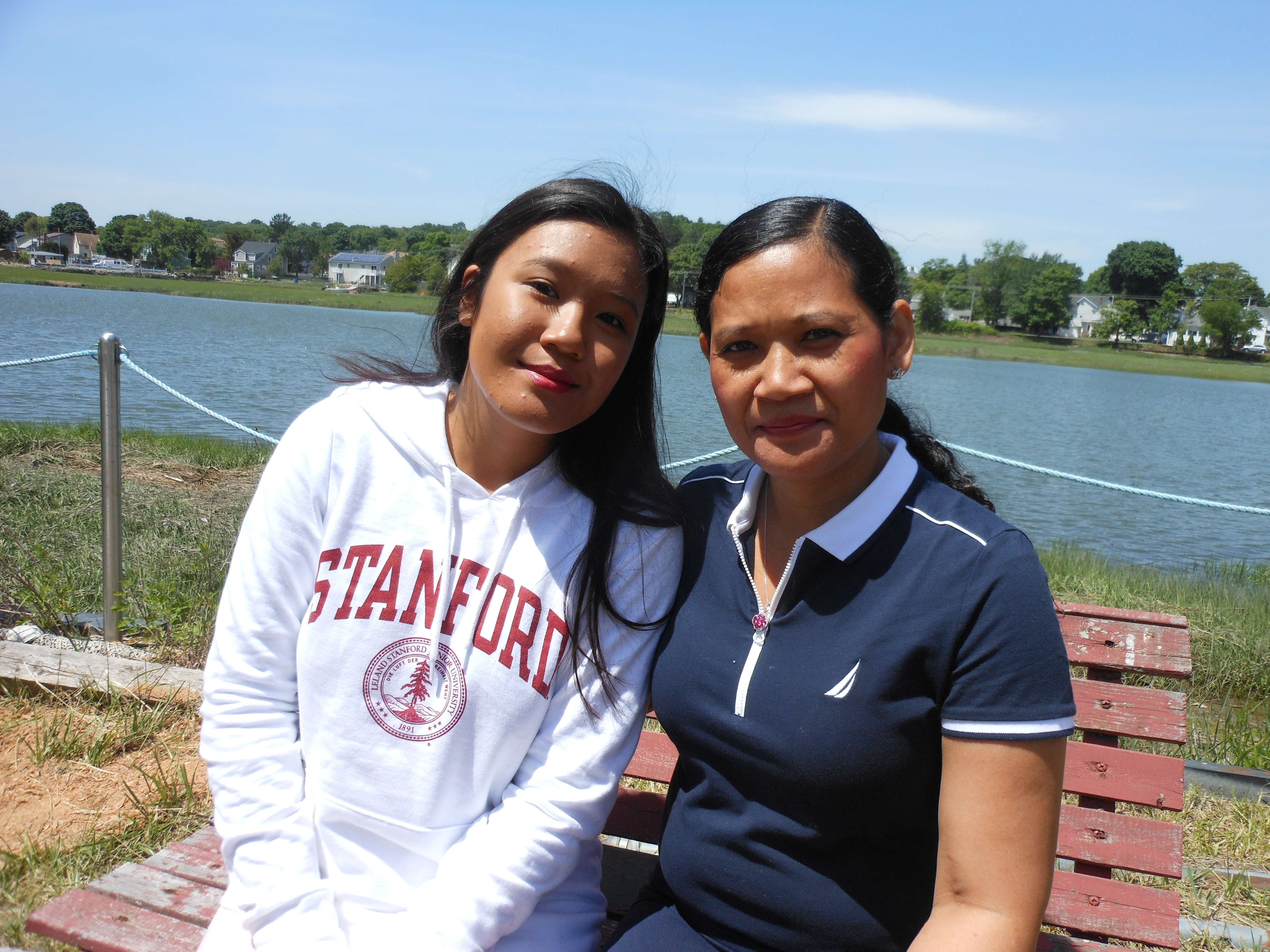 """A STAR STUDENT WITH HER HERO: Victoria Chiek, left, calls her mother, Van Son, her """"biggest hero."""" Chiek credits her educational success – the top of her class at Kipp Academy in Lynn and college-bound on a scholarship to Stanford University in the fall – to her mom, who had her reading at an early age and attending a preschool when she was two years and nine months old. Here, the high school graduate and her mom relax in the backyard near the Saugus River."""