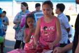 Sisters Gigi and Liana Martinez took turns in a rolling ball carnival game on Elm Street
