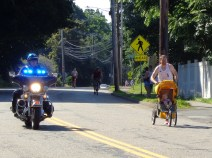 5K winner Shawn Wallace is shown keeping pace with the race's police escort.