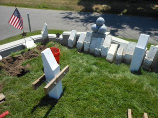 OUT WITH THE OLD: Vietnam War veteran Gordon Shepard – assisted by Andrew DePatto, a summertime cemetery worker, and Tim Fawcett, Jr., a full-time cemetery worker – removed the old marble posts lined up against the wall and replaced them with new posts like the one in front of the orange bucket. These posts will hold future replacement markers that will identify all 25 Civil War soldiers buried with an unknown soldier in the burial plot.