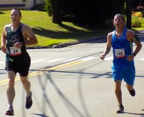 John Langton, 51, (left) and Scott Fitzemeyer, 33, both of Lynnfield, approach the finish line of the the 51st Annual Fourth of July Road Race on Summer Street.