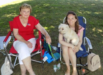 Residents Gail Foley (left) and Emma Swift, with her dog Minnie, watch the 51st Annual Fourth of July Road Race on Summer Street.