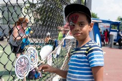 Ali Suliuam added original art to the fence at the tennis court on Tuesday afternoon.