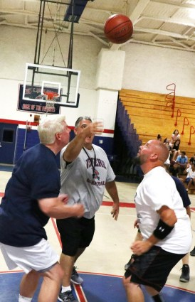 The opening tip-off, Coach Bob Sullivan (center) Alumni George Hurley and Ted Renda fight for first possession.