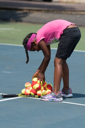 Miykal Sampson collected tennis balls throughout the court, making a neat pile.