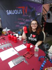 THE TV TABLE: Michelle Madar of Saugus TV shows off the free stuff that the cable television studio handed out to visitors at this year's Founders Day.