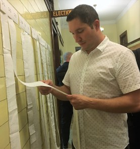 Councillor-at-Large Steven Morabito reads over election results at City Hall on Tuesday night.