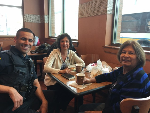 Officer Youness Elalam explains what may be the back story behind Malden resident Anna Viac, at right, and her negative experience with Everett Police during Wednesday's Coffee with a Cop at Market Basket.