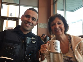 Officer Younness Elalam shares coffee out of a Revere Police mug with Revere resident Marjie Bencivenan during Wednesday morning's Coffee with a Cop at Market Basket.